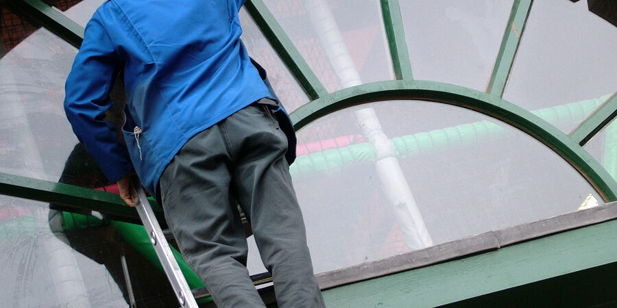 man cleaning windows on ladder at oblique angle