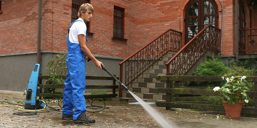 male cleaner pressure washing the concrete way