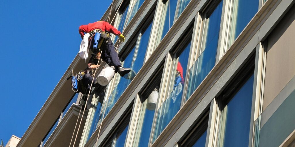 male cleaners cleaning the building window